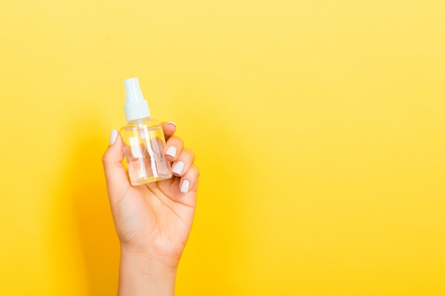 Bottiglia femminile della crema dello spruzzo della tenuta della mano di lozione isolata. la ragazza dà i prodotti cosmetici su fondo giallo