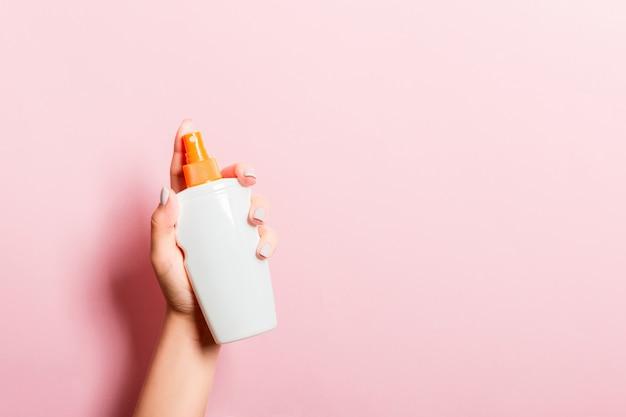 Bottiglia femminile della crema dello spruzzo della tenuta della mano di lozione isolata. la ragazza dà i prodotti cosmetici sul rosa