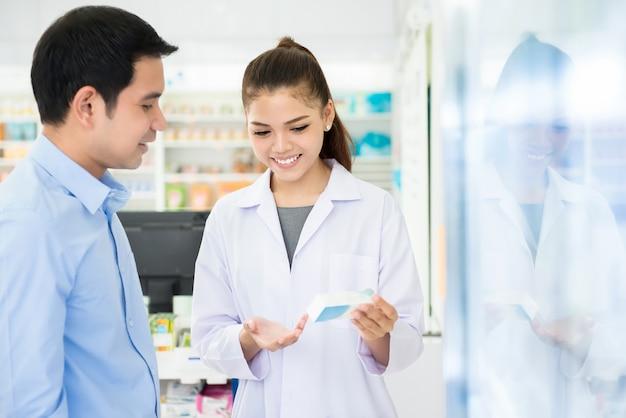 Bottiglia femminile della medicina della tenuta del farmacista che dà consiglio al cliente in farmacia