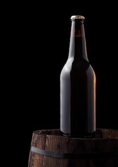 Bottiglia fredda di birra artigianale sul vecchio barilotto di legno su sfondo nero