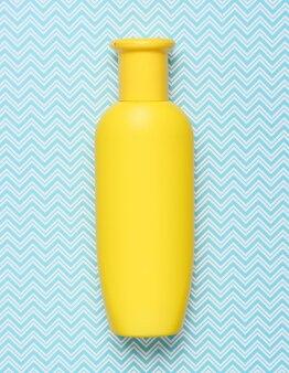 Bottiglia gialla di sciampo sulla vista blu e superiore creativa