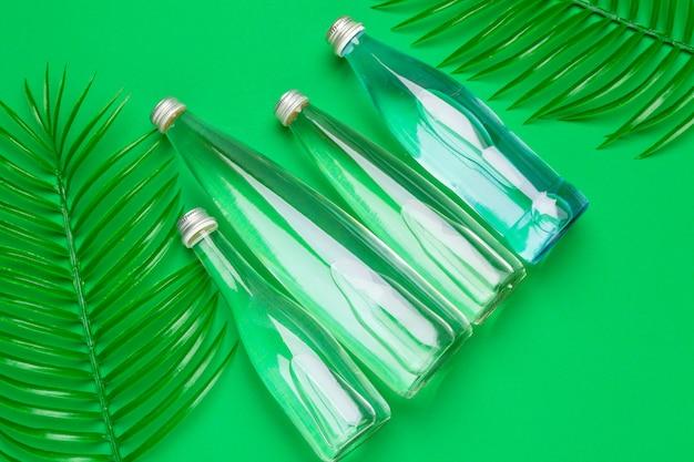 Bottiglia liquida trasparente con foglie di palma tropicali, vista dall'alto