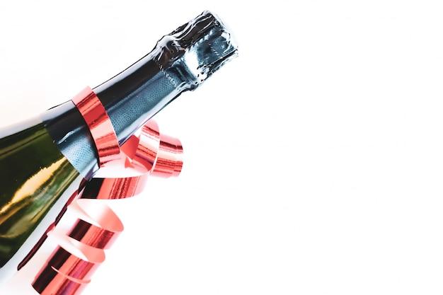 Bottiglia nera di champagne con il nastro rosso su fondo bianco. concetto festivo. stile piatto laico.