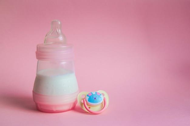 Bottiglia per il latte bambino e tettarella sul rosa