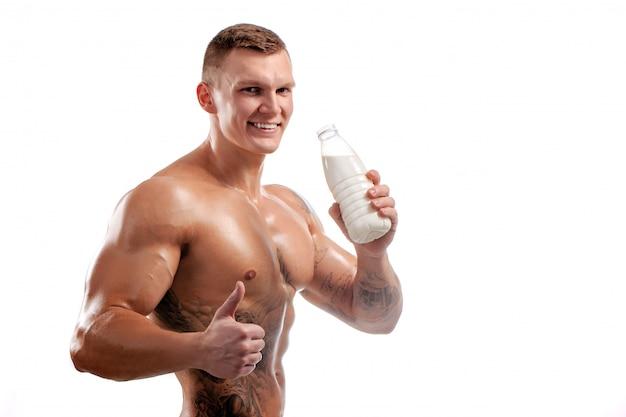 Bottiglia per il latte nelle mani dello sportivo, uomo in buona salute. tatuaggio