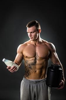 Bottiglia per il latte nelle mani di uno sportivo, uomo in buona salute con il giusto stile di vita. tatuaggio