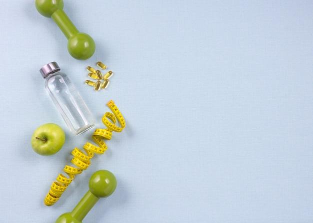 Bottiglia piatta laici d'acqua, nastro di misurazione e mela verde fresca su sfondo blu. concetto di perdita di peso.