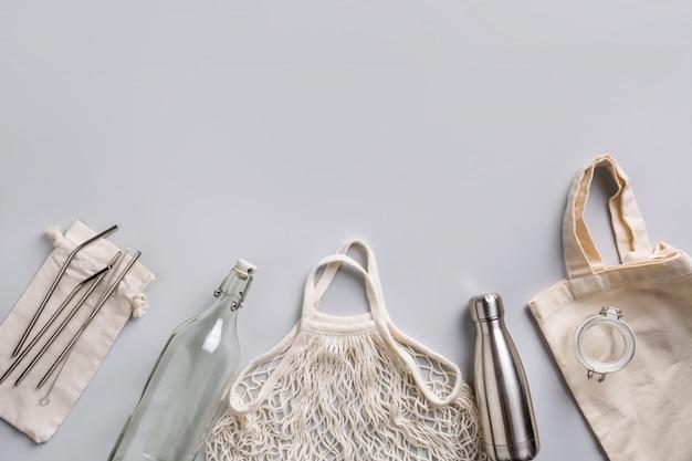 Bottiglia riutilizzabile in vetro e metallo, borsa a rete per uno stile di vita zero rifiuti su grigio