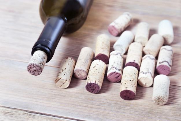 Bottiglia scura di vino con un tappo di sughero sulla tavola di legno invecchiata con lo spazio della copia.