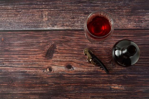 Bottiglia scura di vino e di vetri su fondo di legno. vista dall'alto con lo spazio della copia.