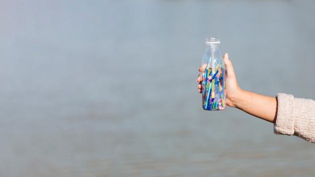 Bottiglia spazio copia con cannuccia di plastica