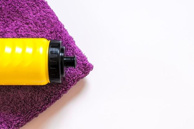 Bottiglia sportiva con un asciugamano isolato su bianco. concetto di stile di vita sano. equipaggiamento sportivo. copia spazio. pianta piatta di accessori fitness e allenamento