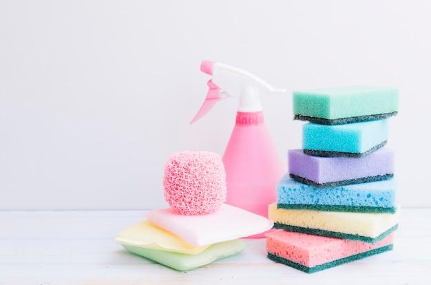 Bottiglia spray rosa con impilati di spugne sulla scrivania in legno