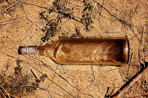Bottiglia trasparente di vetro sopra il pavimento di argilla in esterno, messaggio di ecologia