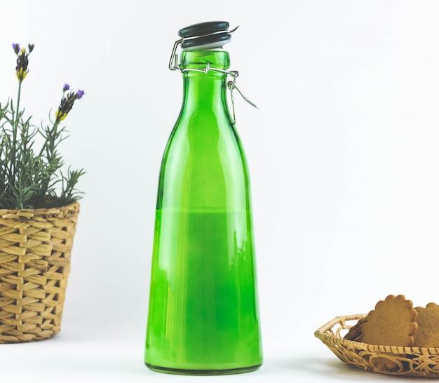 Bottiglia verde con latte e biscotti.