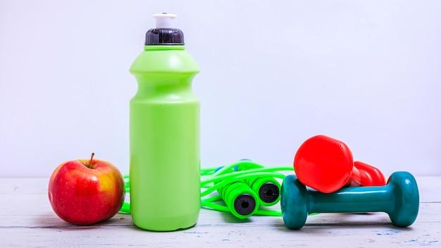 Bottiglia verde di acqua, asciugamano sportivo e attrezzi ginnici isolati su uno sfondo bianco e un tavolo in legno.