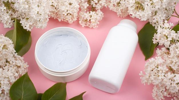 Bottiglie bianche con i cosmetici per il corpo su uno sfondo rosa con il primo piano di fioritura dei lillà dei rami