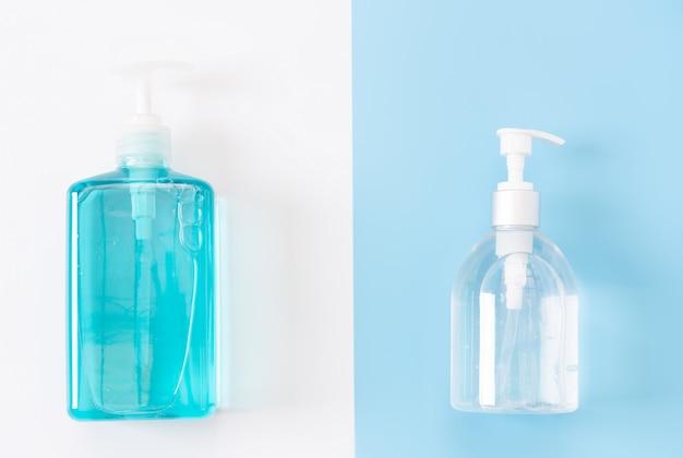 Bottiglie bianche e blu di disinfettante o sapone liquido per igiene delle mani da proteggere dal virus corona su uno sfondo di due toni, vista dall'alto