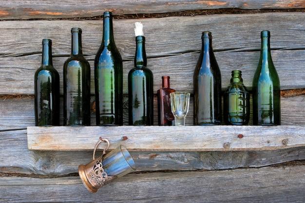 Bottiglie, bicchiere da vino e vetro stanno su una mensola