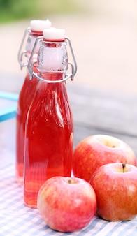 Bottiglie con bevande rosse e alcune mele