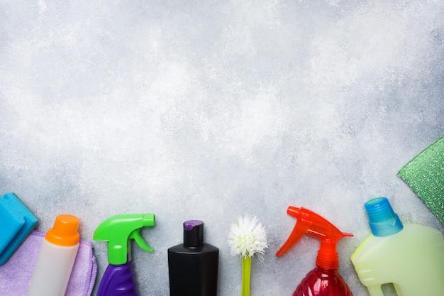 Bottiglie con detergenti, pennelli e spugne su sfondo concreto.
