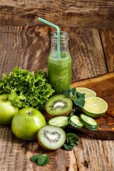 Bottiglie con succhi di verdura fresche sul tavolo di legno