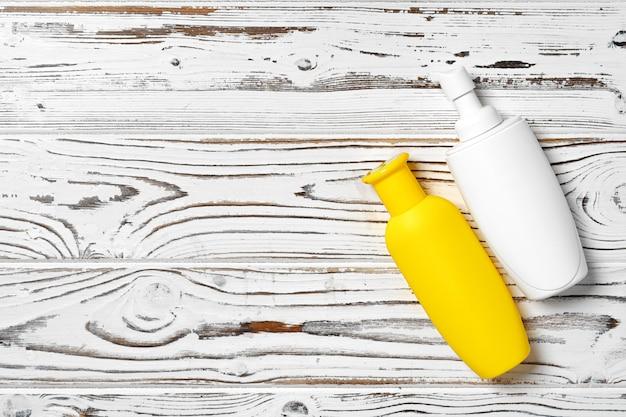 Bottiglie cosmetiche crema di sunblock su superficie di legno