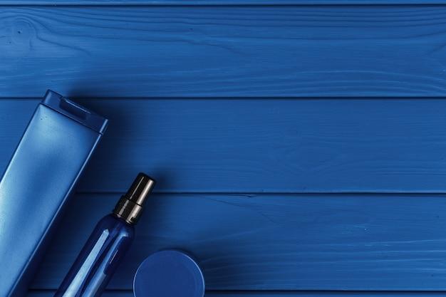 Bottiglie cosmetiche degli uomini sulla tavola blu classica, vista superiore