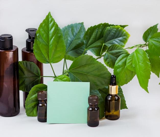 Bottiglie cosmetiche scure e foglie naturali verdi su sfondo chiaro