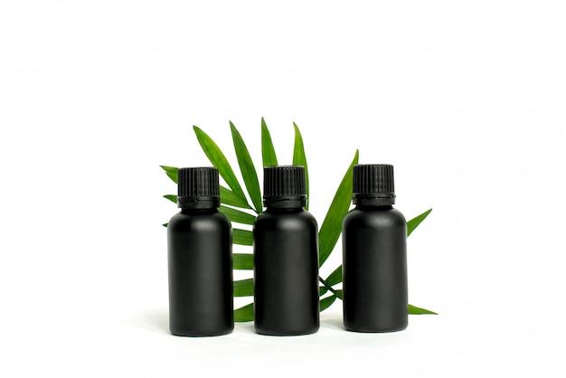 Bottiglie cosmetiche, vasetti di olio nero con foglia di palma verde