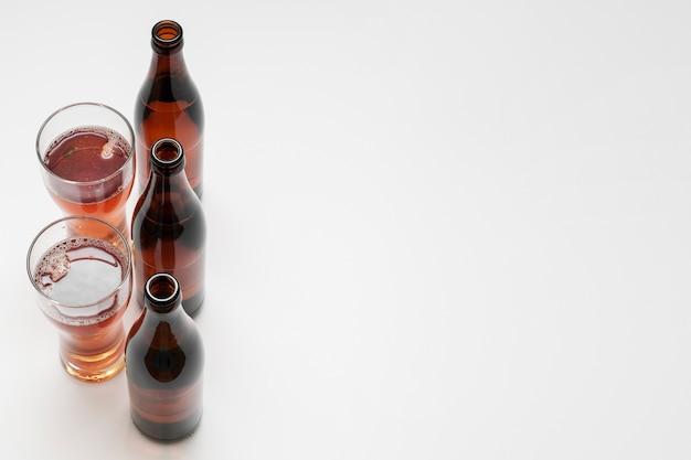 Bottiglie da birra e vetri allineati su fondo bianco con lo spazio della copia