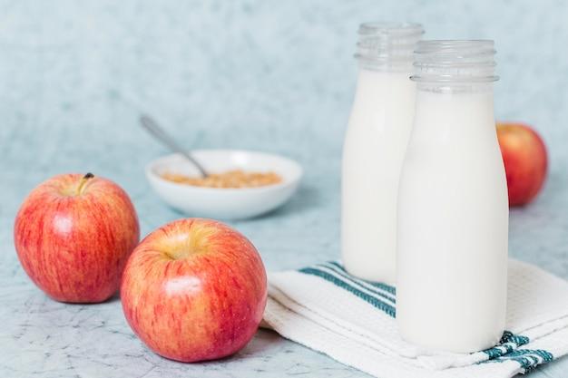 Bottiglie del primo piano con latte e le mele