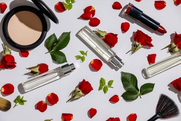 Bottiglie del profumo della donna con i prodotti cosmetici e le rose rosse su bianco