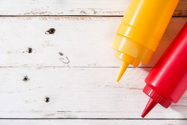 Bottiglie della senape e del ketchup su vista superiore copyspace di superficie di legno bianca