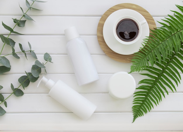 Bottiglie della tazza di caffè e della crema di pelle sopra il fondo bianco dei pannelli