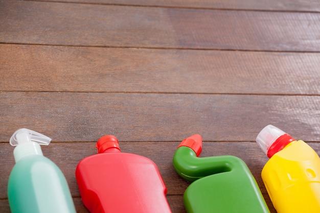 Bottiglie detergenti disposte su uno sfondo di pavimento in legno