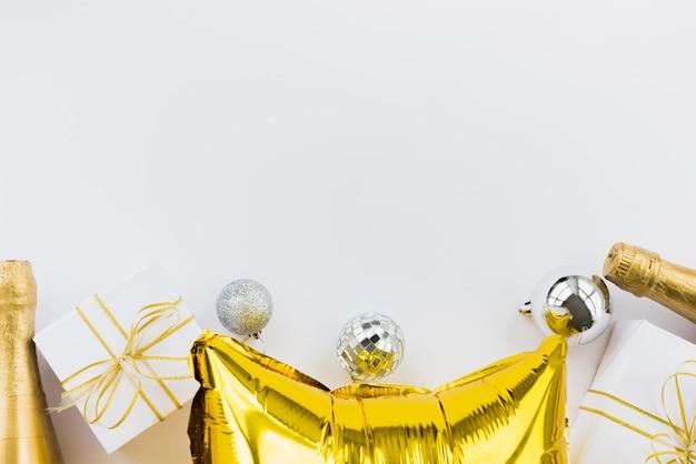 Bottiglie di bevanda vicino a scatole attuali, palle di ornamento e palloncini