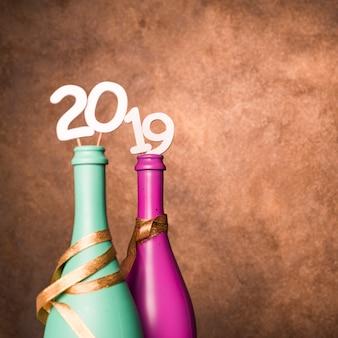 Bottiglie di bevande con numeri 2019 su bacchette