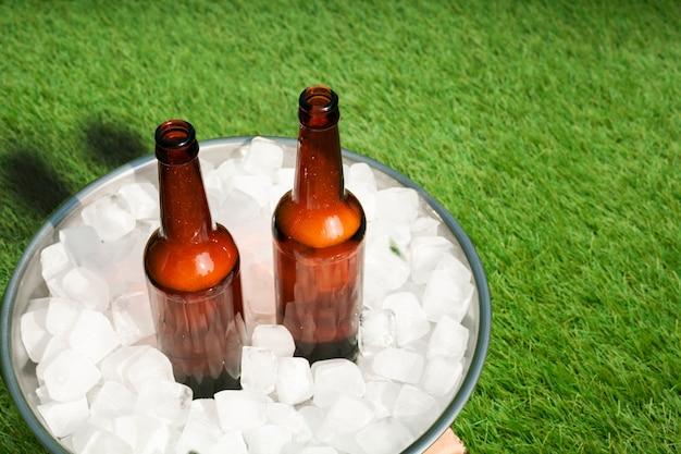 Bottiglie di birra dell'angolo alto in vassoio con ghiaccio