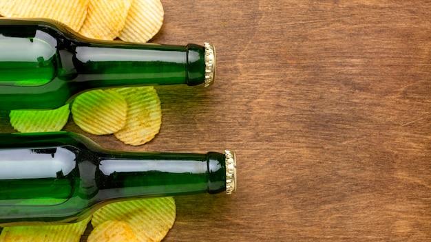 Bottiglie di birra e patatine fritte di vista superiore con lo spazio della copia
