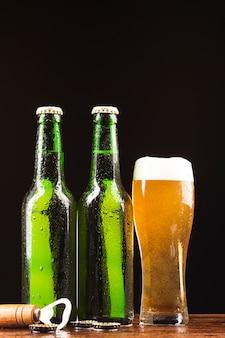 Bottiglie di birra e tazza con apriscatole