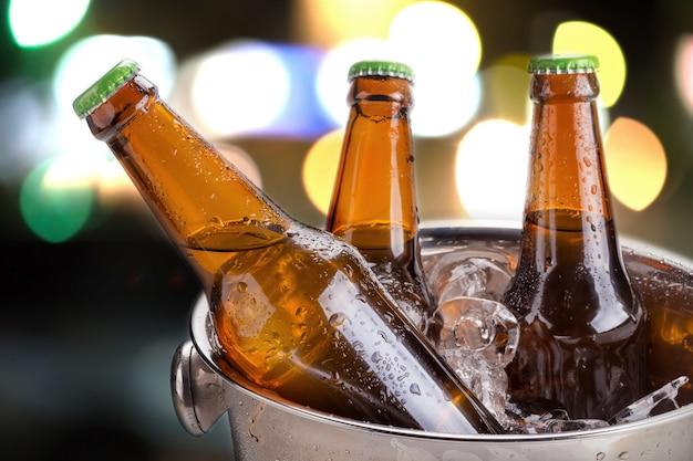 Bottiglie di birra fredda nel secchio con ghiaccio su sfondo bianco