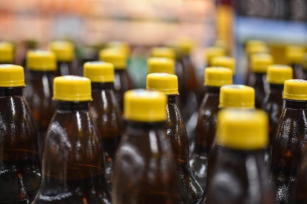 Bottiglie di birra in plastica sul trasportatore di fabbrica