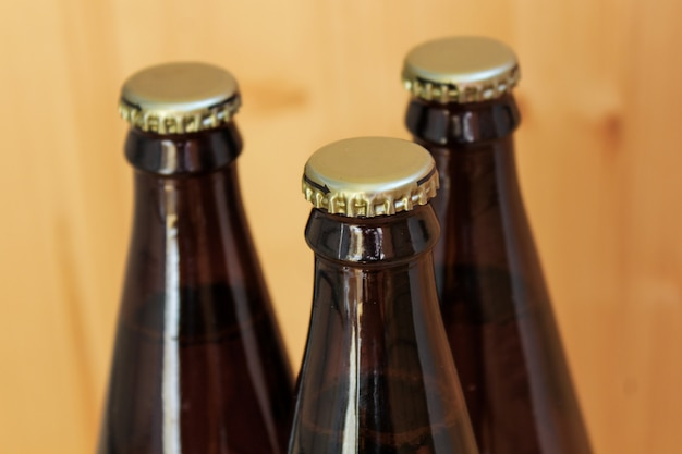 Bottiglie di birra, primo piano raffreddato delle bevande, su fondo di legno