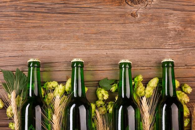 Bottiglie di birra verdi su fondo di legno