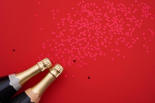 Bottiglie di champagne con cuori di coriandoli su sfondo rosso. copia spazio, vista dall'alto