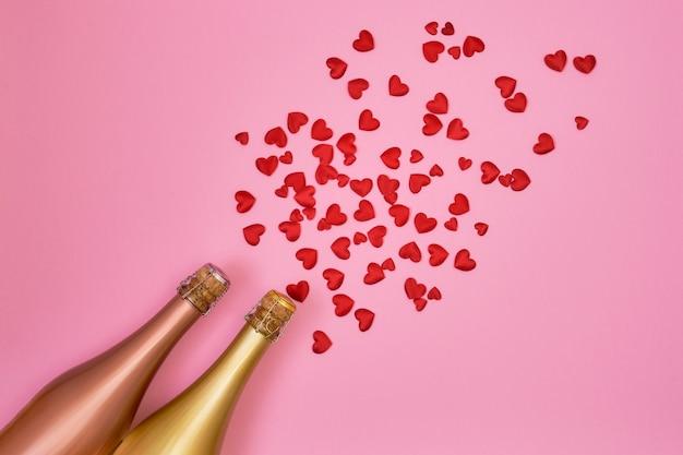 Bottiglie di champagne con cuori rossi su sfondo rosa.