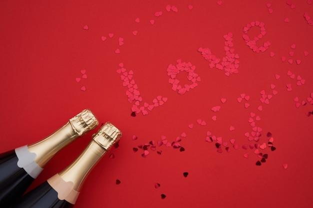 Bottiglie di champagne con i coriandoli che formano parola amore su fondo rosso.