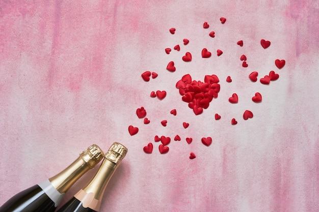 Bottiglie di champagne e cuori rossi su sfondo rosa.