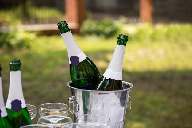 Bottiglie di champagne nel secchio con ghiaccio